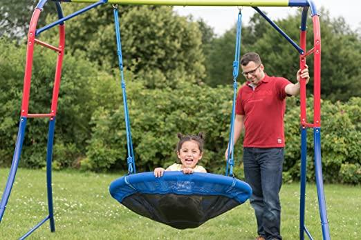 Enfant qui joue sur une balançoire nid d'oiseau avec son père